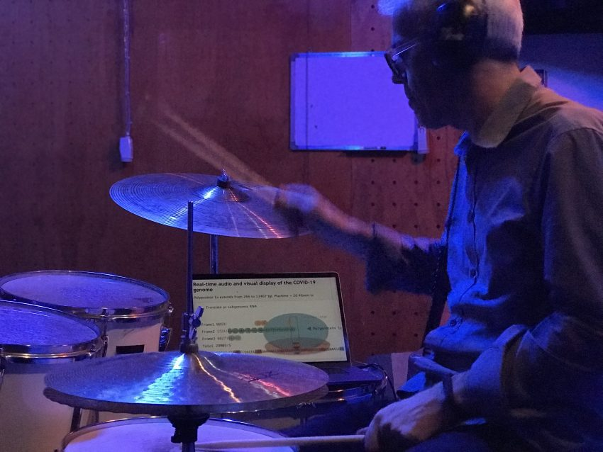 man drumming with computer dashboard in background